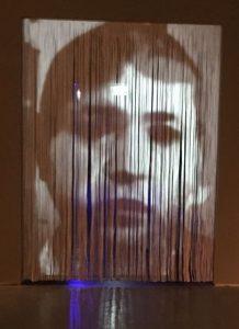 וילון חוטים שעליו מוקרנות פניו של בוטנסקי בגילגוליהן לאורך שנות חייו